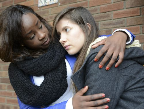 A young woman suffering from depression is consoled by her friend